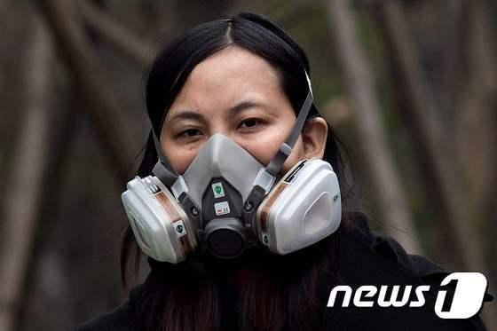20일(현지시간) 중국 베이징에서 한 여성이 미세먼지를 걸러줄 마스크를 쓰고 길을 걷고 있다. © AFP=뉴스1
