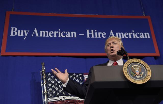 도널드 트럼프 미국 대통령이 18일 위스콘신주 커노샤의 공구제조회사 스냅온에서 '미국산을 사라, 미국인을 고용하라'는 표어 아래 서서 연설하고 있다. 커노샤=AP 연합뉴스