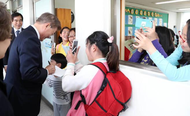 문재인 대통령이15일 서울 은정초등학교에서 행사를 마친 뒤 복도에서 학생들에게 사인을 해주고 있다. 청와대사진기자단