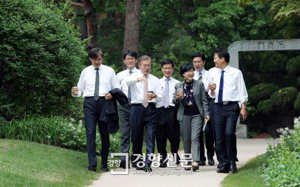 문재인 대통령이 지난달 11일 신임 수석비서관들과 오찬을 갖은 후 커피를 들고 청와대 소공원에서 산책하고 있다./청와대사진기자단
