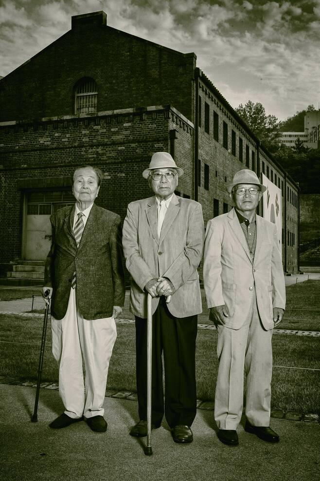 '인혁당 재건위 사건 피해자' 강창덕(1927년생, 왼쪽부터), 전창일(1928년생), 이창복(1933년생) 세 사람이 옛 서울구치소였던 서대문형무소 앞에 나란히 서 있다. 세 사람은 이곳에서 오랜 투옥 생활을 했다
