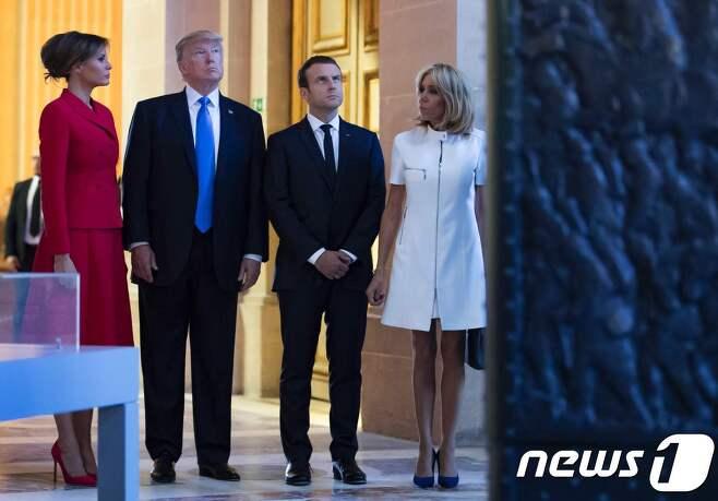 """13일(현지시간) 프랑스 군사기념시설인 앵발리드(Les Invalides)를 방문한 도널드 트럼프 대통령 내외(왼쪽 두 명)과 에마뉘엘 마크롱 내외(오른쪽 두 명) 여기서 트럼프 대통령은 브리짓 마크롱 프랑스 영부인에게 """"몸매가 좋다""""는 인사를 해 물의를 빚었다. © AFP=뉴스1"""