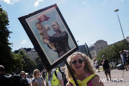 【헬싱키=AP/뉴시스】한 여성이 15일(현지시간) 핀란드의 수도 헬싱키에서 도널드 트럼프 미국 대통령과 블라디미르 푸틴 러시아 대통령의 정상회담 반대 시위에 참석하고 있다. 2018.07.16