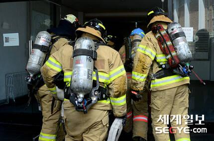 서울 낮 최고 기온이 35도까지 치솟는 등 폭염 특보가 내려진 지난 20일 오후 서울 도심 속 화재현장에서 진화작업을 하기 위해 소방대원이 건물 내부로 들어가고 있다.