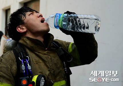 서울 낮 최고 기온이 35도까지 치솟는 등 폭염 특보가 내려진 지난 20일 오후 서울 도심 속 화재현장에서 진화작업을 마친 한 소방대원이 물을 마시고 있다.