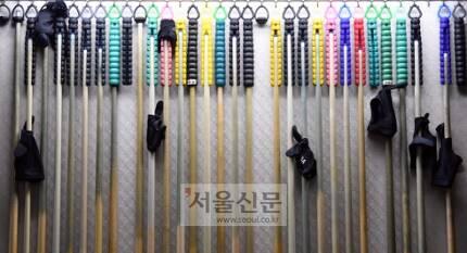 한국당구아카데미에 다양한 모양을 가진 당구큐가 걸려 있다.