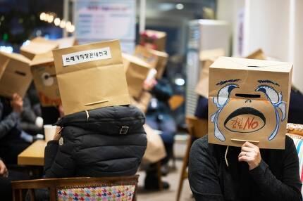 서울 마포구의 한 커피숍에 모인 직장 갑질 피해자 20여명이 종이봉투로 만든 가면을 쓰고 각자의 경험과 노하우를 공유하고 있는 모습. 직장갑질 119 제공