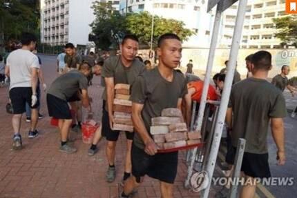 홍콩 시위대가 도로에 설치한 장애물을 치우는 홍콩 주둔 인민해방군 [AFP통신=연합뉴스]