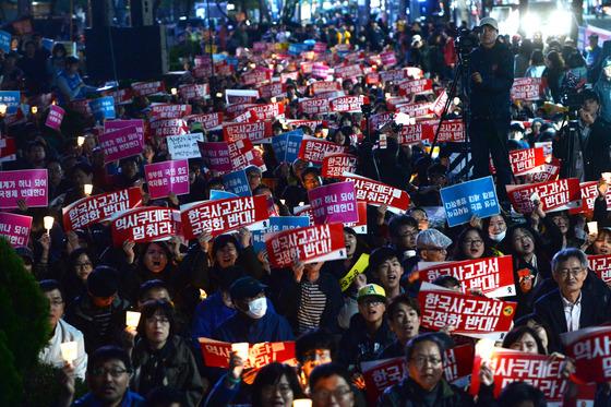 24일 오후 중구 서울 파이낸스 빌딩 앞에서 열린 역사교과서 국정화 저지를 위한 제2차 범국민 촛불문화제에서 참가자들이 촛불을 들고 구호를 외치고 있다. /뉴스1