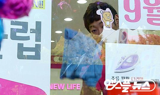 휴대전화 매장 유리를 닦고 있는 박현준(사진=엠스플뉴스)