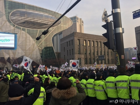 경찰이 박근혜 대통령 탄핵 반대를 외치는 보수단체의 맞불집회와 퇴진을 요구하는 9차 촛불집회 참가자의 충돌을 막기 위해 인간 띠를 만들었다. /사진=방윤영 기자