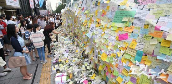 지난 5월 21일 '강남역 묻지마 살인' 추모현장인 서울 지하철 강남역 10번 출구를 찾은 시민들이 추모의 글을 적은 메모지를 붙이고 헌화하고 있다. (사진=황진환 기자)