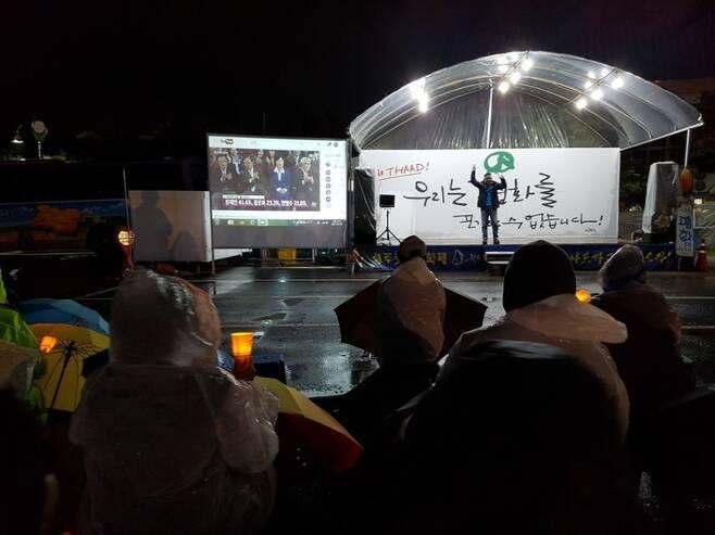 9일 저녁 8시 경북 성주군 성주읍 경산리 성주군청 건너편 주차장에서 열린 301일째 사드 배치 반대 성주 촛불집회에서 주민들이 함께 제19대 대통령선거의 지상파 3사 출구조사 결과를 지켜보고 있다.