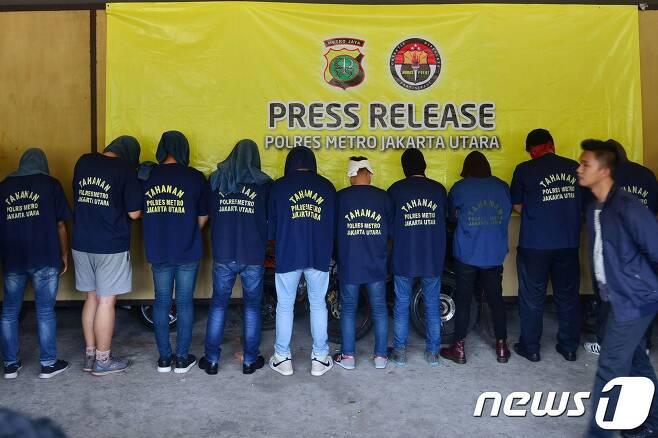 22일(현지시간) 인도네시아 자카르타에 있는 한 경찰서에서 기자회견이 열리는 동안 사우나에서 게이 파티를 했다는 이유로 붙잡혀온 남성들이 뒤돌아서있다. © AFP=뉴스1