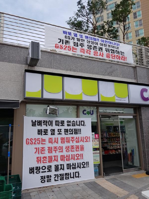 홍영화싸는 14일 자신의 CU편의점 앞에 현수막을 내걸고  인근 GS25편의점 개점 중단을 호소했다.홍영화씨 제공