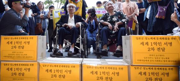 1300번째 수요일… 위안부 할머니, 日대사관에 207만명 서명 전달 - 일본군 위안부 문제 해결을 요구하며 1992년 시작해 26년째 이어지고 있는 '일본군 성노예제 문제 해결을 위한 정기 수요시위'가 13일로 1300회를 맞았다. 이날 서울 종로구 수송동 주한 일본대사관 앞에서 열린 1300차 수요시위에서 휠체어를 탄 김복동(왼쪽·91) 할머니와 길원옥(89) 할머니가 일본군 성노예제 문제 해결을 촉구하는 내용의 '세계 1억인 서명운동' 2차분 155개국 206만 9760명의 서명지를 일본대사관 측에 전달하고 있다. 박지환 기자 popocar@seoul.co.kr