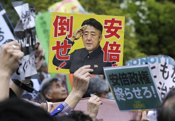 14일 도쿄 나카타초 국회의사당 앞에서 열린 '아베 정권 퇴진' 집회에서 참가자들이 '아베를 무너뜨려라', '아베 정권을 끝내라'고 적힌 플래카드를 들고 있다.[EPA=연합뉴스]