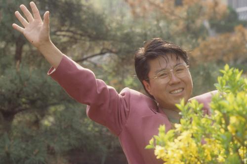 봄을 맞아 꽃밭에서 해맑은 표정으로 손을 흔드는 조용필. [중앙포토]