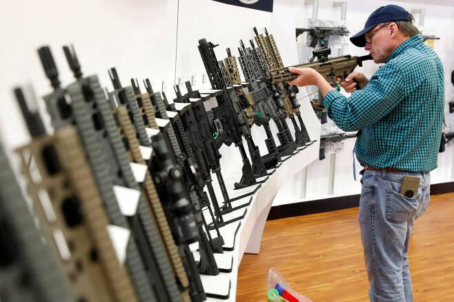 전시장 진열된 반자동 소총을 한 남성이 살펴보고 있다. [로이터=연합뉴스]