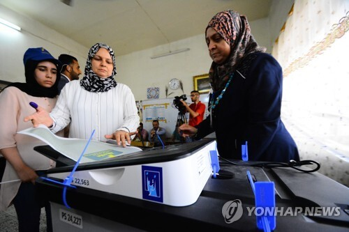 전자 투개표 시스템에 투표용지를 넣는 이라크 유권자[DPA=연합뉴스자료사진]