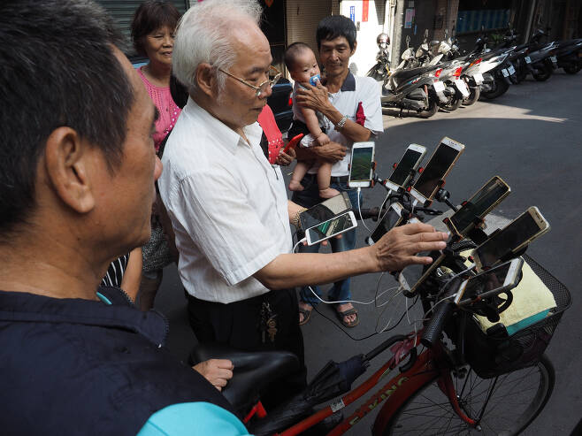 풍수 전문가 첸 산 위안이 8일(현지시간) 대만 신베이시 거리에서 주민들에게 11대의 스마트폰을 장착한 자전거를 보여주고 있다. [EPA=연합뉴스]