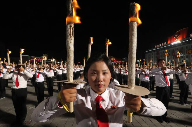 횃불을 든 북한 여학생이 행진준비를 하고 있다. [타스=연합뉴스]