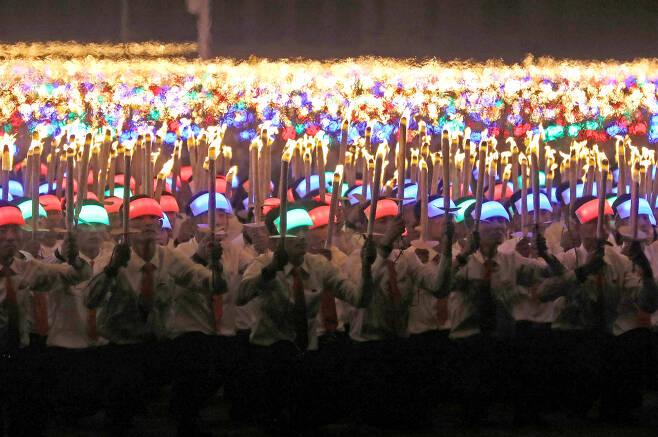 어린 학생들이 머리에 조명띠를 두르고 행진하고 있다. [타스=연합뉴스]