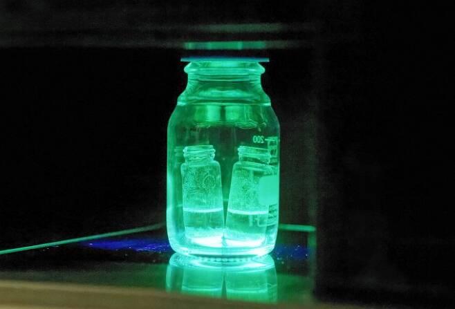 물의강한 페로브스카이트의 모습이다. 기존에는 물에서 특성을 잃었지만 연구진이 수산화막 보호막을 씌우자, 물속에 담가도 자외선에 반응해 발광하는 특성을 유지한다. -울산과학기술원 제공