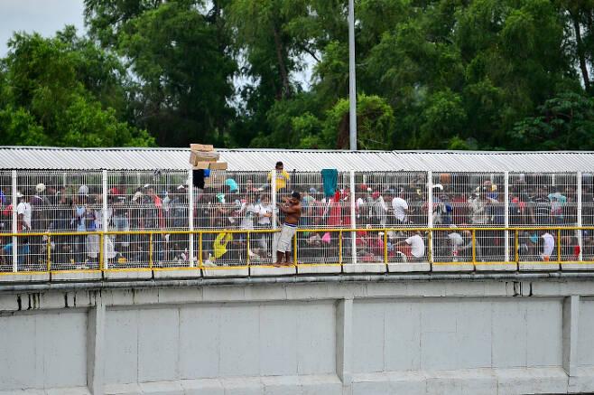수치아떼 강 위 다리에 위태롭게 매달린 온두라스 이민자.  AFP=연합뉴스
