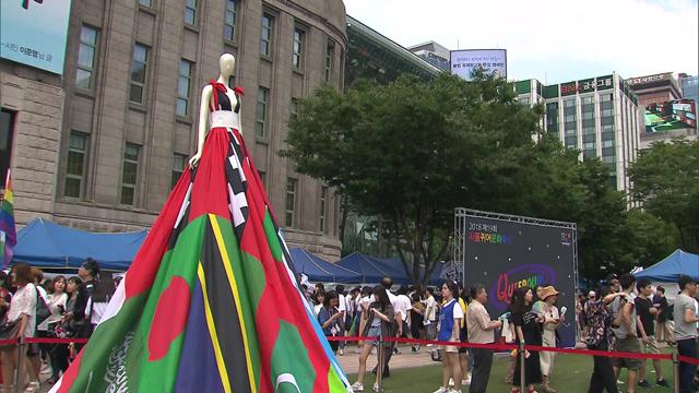 2018년 서울퀴어문화축제 때 서울광장에 설치됐던 '레인보우 드레스'. 네덜란드 예술가들이 만든 3.5미터의 대형 드레스로, 성소수자를 형사 처벌하는 75개 국가의 국기를 모아 만들었다. 어떤 나라에서 성소수자 처벌법이 폐지된다면, 해당 국가의 국기를 레인보우기로 바꾼다.