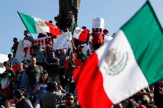 멕시코 시민들이 18일(현지시간) 티후아나 시에서 멕시코 국기를 흔들며 이민자 반대 시위를 벌이고 있다. [로이터=연합뉴스]