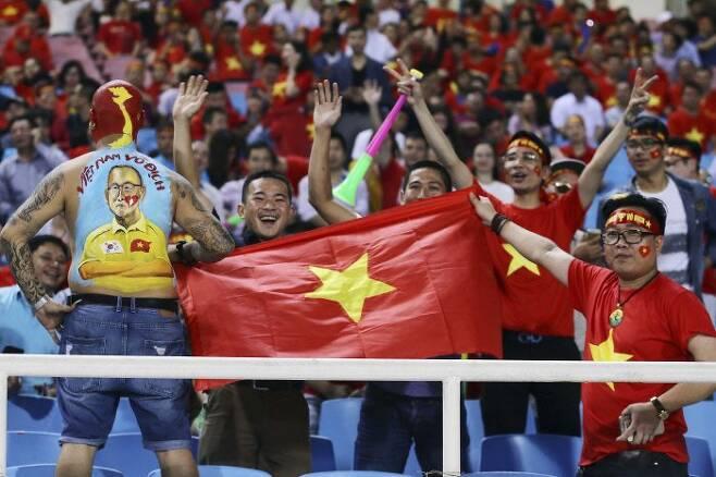 베트남 팬들이 6일(한국시간) 2018 스즈키컵 준결승 2차전 필리핀과의 결기 중 열띤 응원을 하고 있다. 한 관중의 등엔 박항서 감독의 얼굴이 새겨져 있다. AP연합