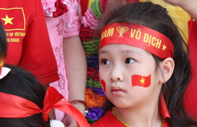4일 오전(현지시간) 아랍에미리트 아부다비 국제공항에서 한 베트남 어린이가 '무적 베트남'이라는 뜻의 '보딕 베트남(vo dich Vietnam)을 쓴 붉은색 머리띠를 하고 박항서 베트남 축구대표팀 감독과 선수들을 기다리고 있다. [연합뉴스]