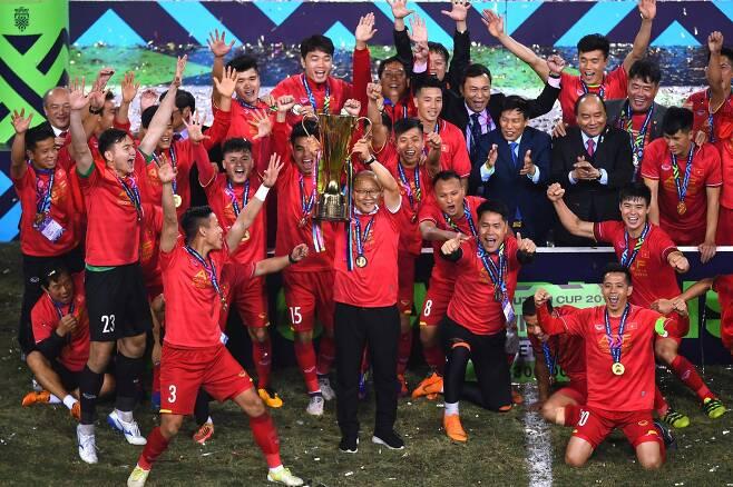 지난해 10월 베트남 대표팀 감독에 취임한 박 감독은 연일 베트남 축구의 역사를 새로 쓰며 '국민 영웅' 반열에 올랐다. 박 감독은 10년 만의 결승 진출에 이어 우승까지 이끌어 베트남을 열광의 도가니에 빠뜨렸다. 국내에선 2002 월드컵 한국의 4강 신화를 지휘한 거스 히딩크 감독에 빗대 '쌀딩크'라는 애칭으로 불리며 베트남과 동남아 축구에 대한 관심을 키우고 있다.사진은 지난해 12월 15일(현지시간) 베트남 하노이에서 스즈키컵에 우승한 박항서 감독이 트로피를 높이 들며 선수들과 기뻐하고 있는 모습. [AFP=연합뉴스]