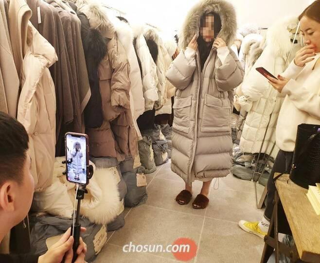 지난 2일 자정쯤 서울 중구 의류도매상가 APM플레이스에서 중국인 보따리상 BJ(왼쪽)가 휴대폰으로 쇼핑 생방송을 진행하고 있다. 중국에서 방송을 보던 시청자들이'모자 쓴 모습도 보고 싶다'는 실시간 댓글을 달자 매장 직원(가운데)이 패딩 모자를 써보고 있다. /이건창 기자