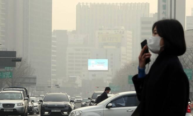 14일 오전 마스크를 쓴 시민 뒤로 미세먼지 탓에 뿌옇게 흐려진 서울 광화문 일대가 보이고 있다. 박종식 기자 anaki@hani.co.kr