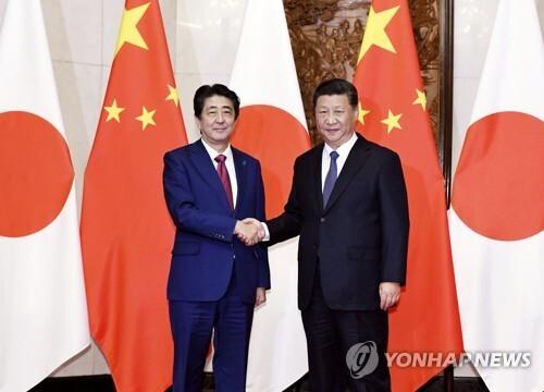 시진핑(習近平·오른쪽) 중국 국가 주석과 아베 신조(安倍晋三) 일본 총리가 작년 10월 중국 베이징(北京)에 있는 조어대(釣魚台)에서 회담을 하기에 앞서 악수를 하는 모습 [교도=연합뉴스 자료사진]