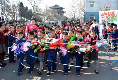 (평양 조선중앙통신=연합뉴스) 2017년 평양 시내 한 소학교 입학식에서 신입생들이 선배들의 박수를 받으며 운동장에 들어서고 있다.