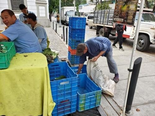 시장에서 야채 부스러기를 줍는 한 시민 [연합뉴스]