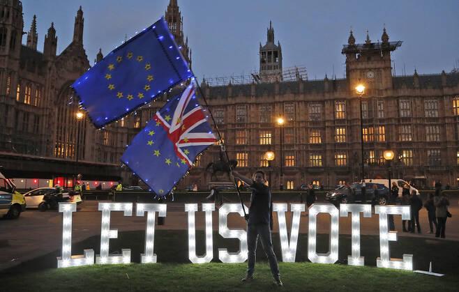 """27일 저녁 영국 하원이 브렉시트 대안 8개안에 대한 표결을 진행하던 시각에 의사당 바깥에 글로벌 시민단체 아바즈가 """"우리가 투표하게 하라""""는 주장을 담은 전광 불빛이 빛나고 있다. 런던/AP 연합뉴스"""