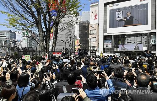나루히토(德仁) 일왕시대 연호 '레이와(令和)' (도쿄 로이터=연합뉴스) 1일 일본 도쿄에서 시민들이 오는 5월 1일 시작되는 새 나루히토(德仁·59) 일왕 시대의 연호(年號)로 '레이와'(令和)가 선정됐음을 발표하는 대형 TV 보도 화면을 휴대폰 카메라에 담고 있다. bulls@yna.co.kr