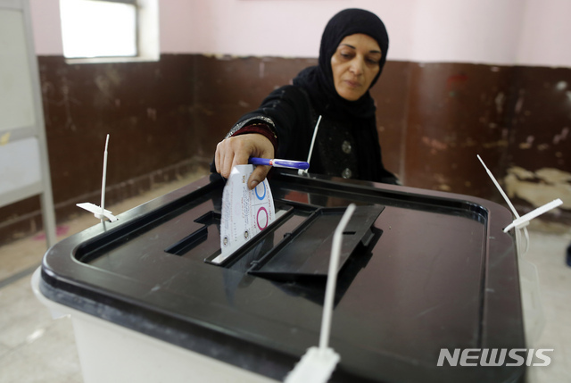 A voter casts her ballot on constitutional amendments during the first day of three-day voting at a polling station in Cairo, Egypt, Saturday, April 20, 2019. Egyptians are voting on constitutional amendments that would allow President Abdel-Fattah el-Sissi to stay in power until 2030. (AP Photo/Amr Nabil)