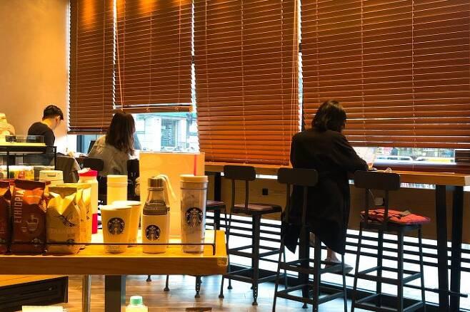 (사진=스냅타임) 스타벅스 창가 스탠드업 테이블에서 콘센트를 이용 중인 카공족들