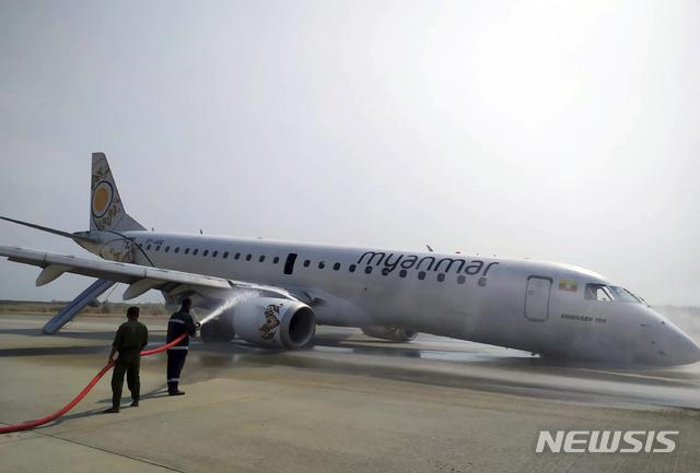 【만달레이=AP/뉴시스】12일(현지시간) 미얀마 만달레이 공항에서 소방관들이 기체 앞부분으로 착륙한 미얀마 항공 여객기에 물을 뿌리고 있다. 이 항공기는 이날 착륙 장치 고장으로 비상착륙했지만 탑승자 82명 전원 무사한 것으로 알려졌다. 2019.05.12