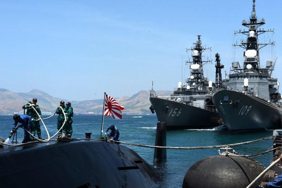 영유권 분쟁 지역인 남중국해와 가까운 필리핀 수빅항에 일본 해상자위대 잠수함 오야시오가 입항한 가운데 대원들이 잠수함 갑판 위에서 작업하고 있다. 뒤로는 오야시오 를 호위하고 온 구축함 세토기리(왼쪽)와 아리아케가 정박해 있다. 자위대 잠수함이 필리핀에 입항한 것은 2001년 이후 15년 만이다. 필리핀은 중국의 남중국해 군사기지화를 견제하기 위 해미국,일본과군사협력을강화하고있다. 2016.4 AFP 연합뉴스