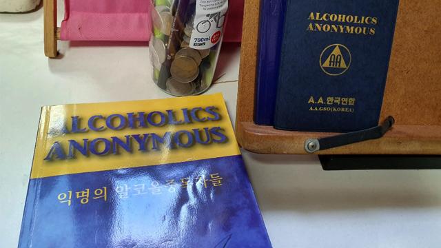 A의 책상 위에 A·A(익명의 알코올 중독자들) 서적과 수첩이 놓여져 있다. N·A는 A·A에서 파생돼 나온 조직이다. A·A는 국내에 9개 지역 지부가 있을 정도로 활발하게 운영되지만 N·A는 공식적으로 전국 4곳만 운영되고 있다.