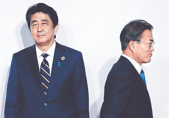 문재인 대통령이 28일 일본 오사카에서 열린 G20 정상회의 환영식에서 아베 신조 일본 총리(왼쪽)와 8초간 악수한 뒤 이동하고 있다. [청와대사진기자단]
