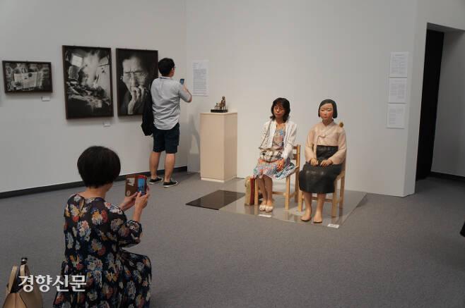 한 관람객이 1일 일본 나고야 아이치예술문화센터에서 개막한 '아이치 트리엔날레 2019'의 '표현의 부자유-그후'에 전시된 '평화의 소녀상' 옆에 앉아 사진촬영을 하고 있다. 나고야|김진우 특파원