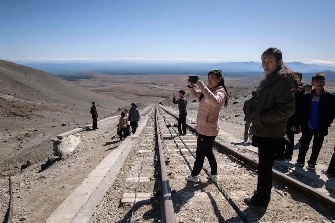 지난 11일 북한 주민들이 케이블 기차를 이용해 백두산 전망대에 도착한 후 열차에서 내려 기념촬영을 하고 있다. [AFP=연합뉴스]