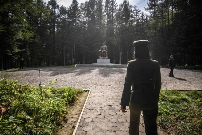 지난 12일 한 안내원이 삼지연의 비밀 캠프로 가는 길에 있는 김일성 주석 동상으로 안내하고 있다. [AFP=연합뉴스]